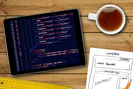 website wireframe sketch and programming code on digital tablet screen