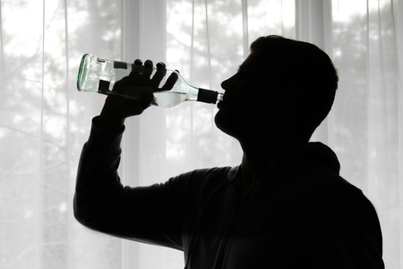 alcoholism: alcoholism - silhouette of man drinking alcohol Stock Photo