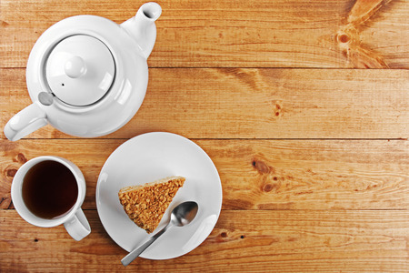 tea and biscuits: piece of cake and tea pot on wooden table