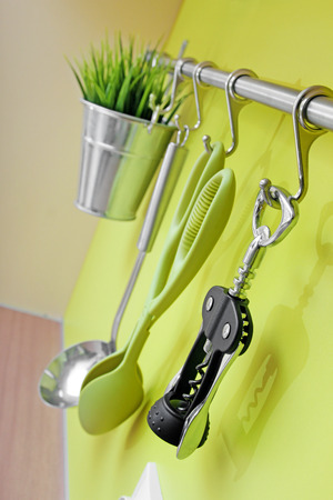 daily use item: kitchen utensils hanging on green wall