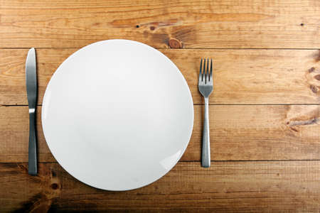 empty plate: empty white plate on brown wooden table