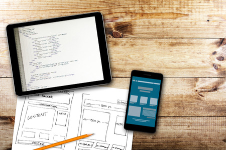development process: website wireframe sketch and programming code on digital tablet