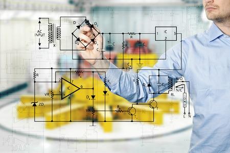 ingeniero: ingeniero eléctrico dibuja un diagrama de un circuito. planta de energía interior en el fondo Foto de archivo
