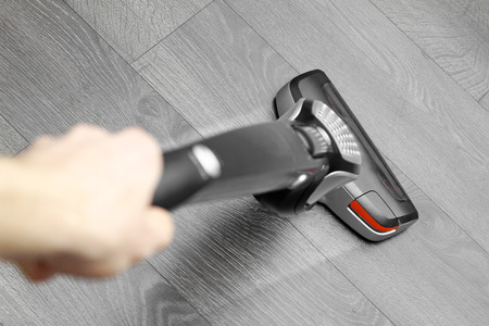 cleaning floor with cordless vacuum cleaner Stockfoto