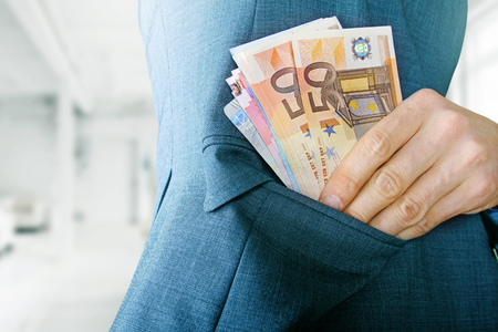 putting money in pocket: corruption concept, man putting money in jacket pocket Stock Photo