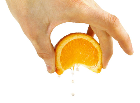 squeeze orange in hand, isolated on a white