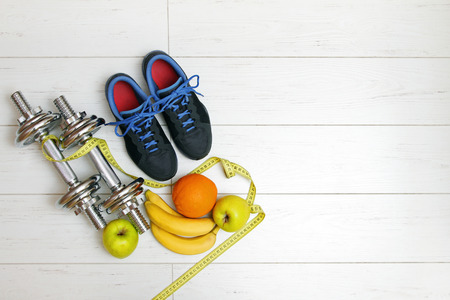 fitness equipment and fruits on white wooden plank floor