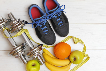 wooden shoes: fitness equipment and healthy nutrition on white wooden plank floor Stock Photo