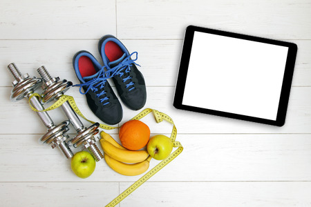 fitness equipment, fruits and blank digital tablet on white wooden floor