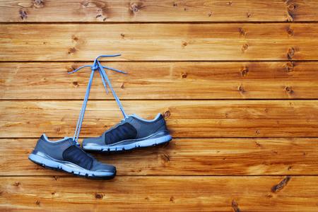 chaussure: paire de chaussures de sport pendre � un clou sur un mur en bois brun Banque d'images