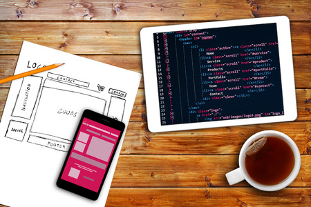 table of contents: website wireframe sketch and programming code on digital tablet