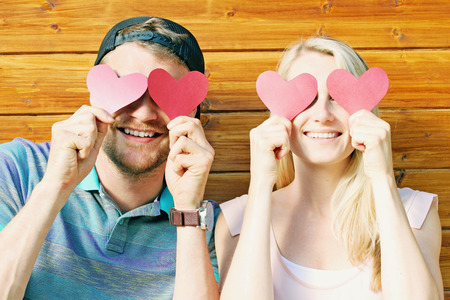 ladies day: fall in love concept - young couple holding paper hearts over eyes