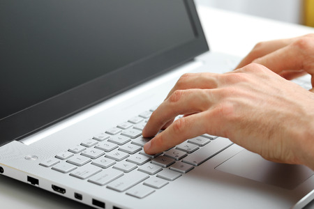 hands typing on laptop keyboard Imagens
