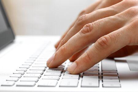 white laptop: dita digitando sulla tastiera di un computer portatile bianco Archivio Fotografico