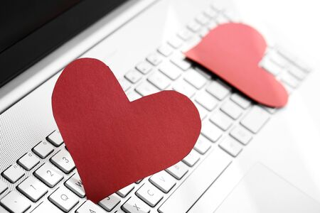 internet dating: internet dating concept - two paper hearts on computer keyboard