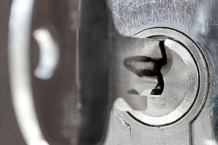 lock concept: macro shot of door lock keyhole with key