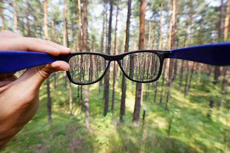 transparente: anteojos ópticos en la mano sobre fondo de bosque borrosa