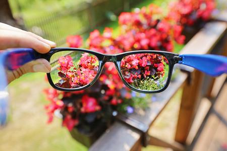 optical eyeglasses in the hand over blurred flower background Stockfoto