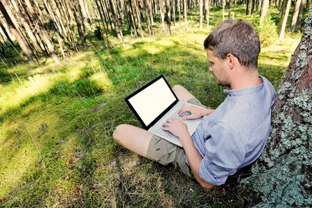 people relaxing: man is sitting against a tree in the forest, working with his laptop