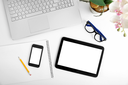 workspace with laptop, blank digital tablet and smartphone on white table
