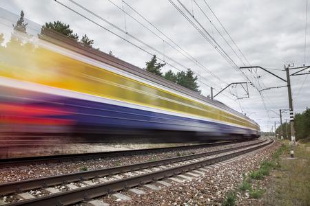 passenger train on railroad tracks in speed motion
