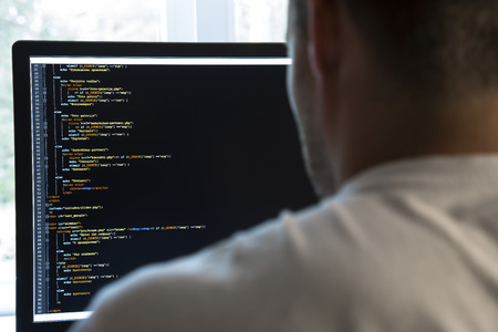 programmer from behind and programming code on computer monitor. focus on monitor Stock Photo