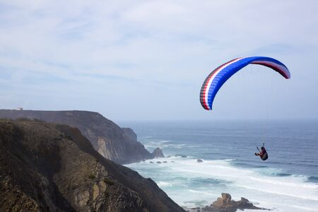 extreme sports: paragliding above the ocean at Castelejo beach in Portugal