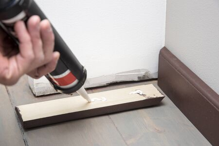 skirting: home improvement, pushing glue on the wooden baseboard Stock Photo