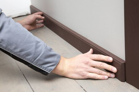 baseboard: installation of a brown wooden baseboard at the bottom of the wall Stock Photo