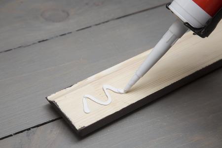 pegamento: poniendo pegamento en un trozo de madera de la placa base Foto de archivo