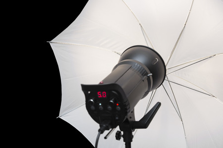 strobe: photography studio strobe flash with white umbrella and black copy space