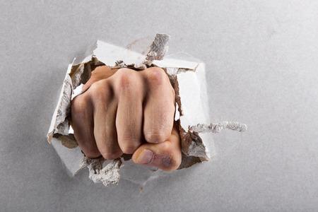 pared rota: concepto de la agresión, la pared se rompe a través de un puño
