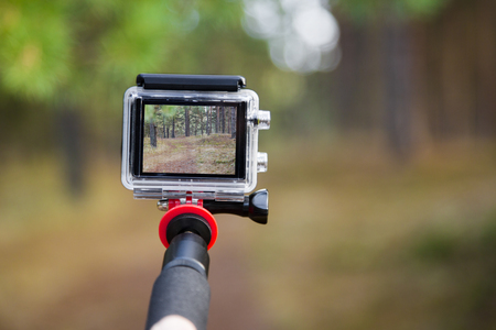 taking video with action camera on handheld stick 写真素材