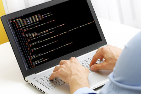 programmer profession - man writing programming code on laptop computer
