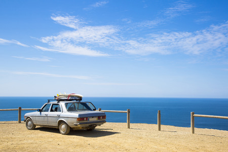 old retro car with surfboards on the roof and ocean in background Stock Photo