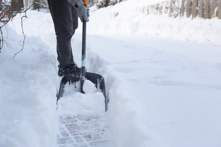 yard: man shoveling snow away from walkway
