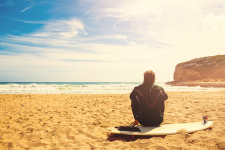 perfect waves: surfer on the beach waiting for perfect waves