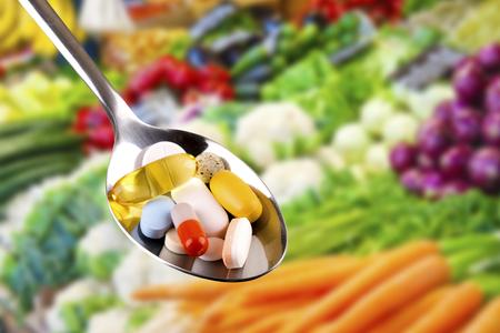 野菜の背景に栄養補助食品の錠剤とスプーン
