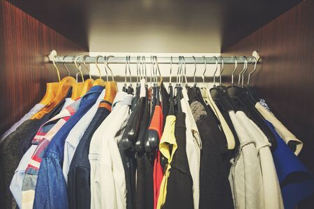 closets: variety of clothes hanging in wooden wardrobe