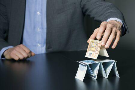 esquema: hombre de negocios la construcción de la pirámide financiera de dinero del euro