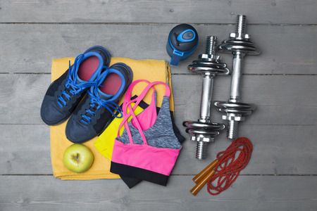 top view of colorful fitness equipment on wooden floor. Stock Photo