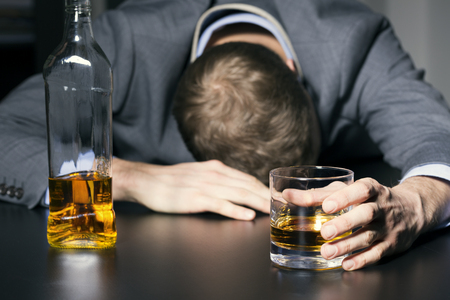 emotional: alcohol addiction - drunk businessman holding a glass of whiskey