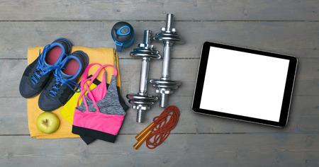 fitness: kleurrijke fitnessapparatuur en lege digitale tablet op de sportschool vloer Stockfoto