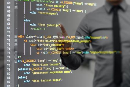 Mann auf virtuellen Bildschirm zeigt mit Website-Programmierung Code