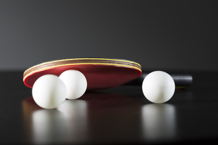 tischtennis: Tischtennisschläger und Bälle auf einem dunklen Tisch