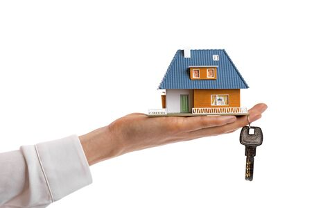 hand key: buying new real estate concept, small family house and key on womans hand Stock Photo
