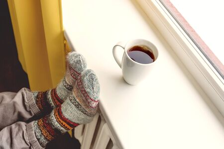 heat home: warming by the radiator and drinking hot tea Stock Photo