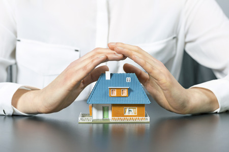residential building insurance: real estate insurance concept - human hands saving small house