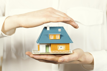 hand hovering small family house, home insurance concept Stock Photo