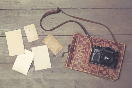vintage photo: old retro camera on vintage photo album and blank pictures